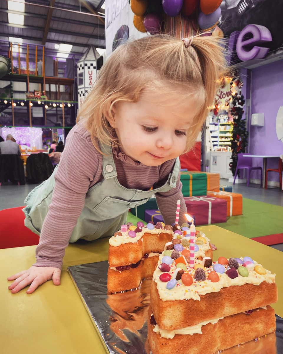 Pearl Pentland blowing out her birthday candles at a colourful soft play centre. Pearl is leaning over the table to reach her cake.